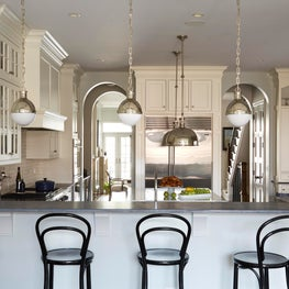 White kitchen with black bar stools, polished nickel, gray countertops