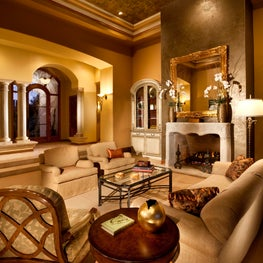 Traditional, elegant formal living room in golds, greens with stone fireplace