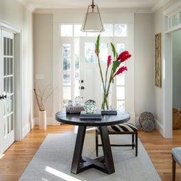 Modern neutral foyer w center table, shade pendant, zebra bench