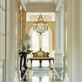 Grand Entrance with custom marble floors, round settee and high gloss walls.