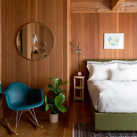 post and beam/green upholstered bed/eames rocking chair/mid century mod bedroom