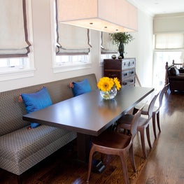 banquette is a comfortable and surprising way to anchor a dining table, and the sculptural wooden chairs are a great contrast.