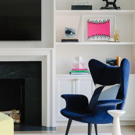 Punchy family room with sculptural furniture and citron ottoman