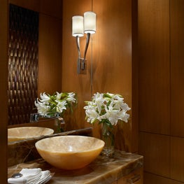 A beige pedestal sink in smooth stone adds to this wood paneled powder room.