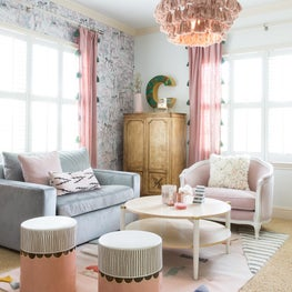 Bright master bedroom seating area with pink and blue chairs, tassel chandelier, and poufs
