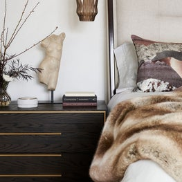 Cozy modern bedroom design with plaster walls, hanging pendant lights, and warm elements