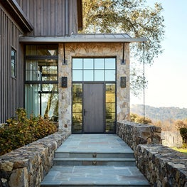 Modern rustic exterior with stone and cedar board and batten