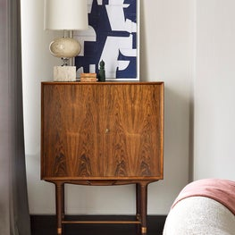 Artful living room with mid-century lamp and bar cabinet and custom silk carpet.