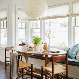 Coastal blue and white breakfast area with mid century furniture