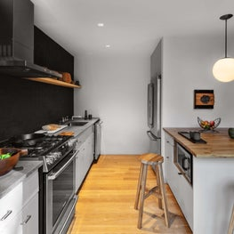 Kitchen with orb pendant, cool grey walls, open shelving, wood block island