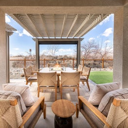 Patio with outdoor furniture and kitchen, dining table and chairs, ottomans, cushions and sun shade screens