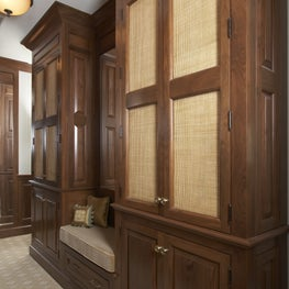 Custom hardwood closets and drawers with a built-in bench and neutral carpeting.