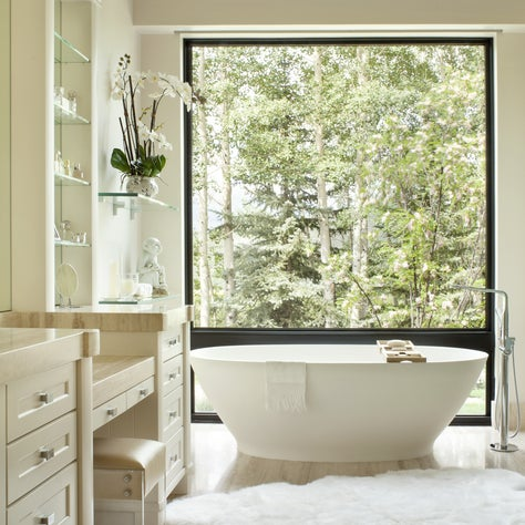 Neutral, off-white bathroom with standing tub and fur rug.