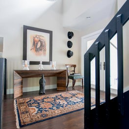 Double-height Miami foyer features glass doors and eclectic vintage elements