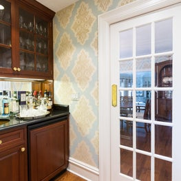 Vignette of a well-appointed butler's pantry with pastel patterned wallpaper.