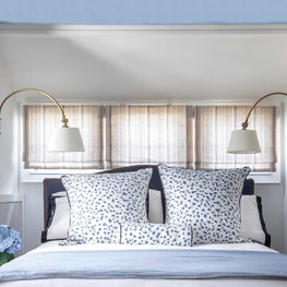Upholstered navy bed w/ striped linen roman shades, blue leopard shams,