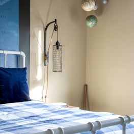 A nautical bedside lamp and hanging planet decor in the corner of a boys bedroom in Houston, Texas