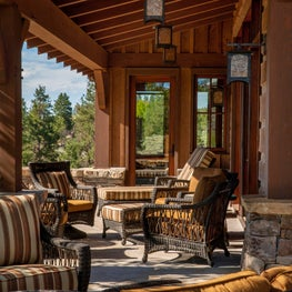 Mountain house front porch with woven armchairs and hanging lanterns