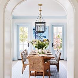 Blue and white dining room with hanging lanterns and painted trim