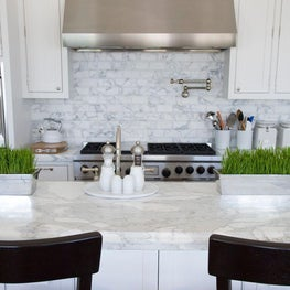 The kitchen features a professional-grade range and range hood.