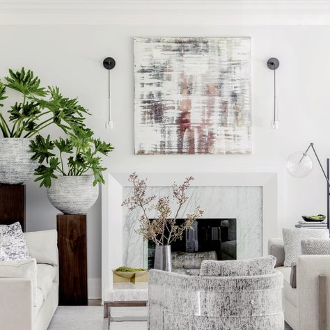 Modern living room with acrylic chair, sleek fireplace, and abstract art