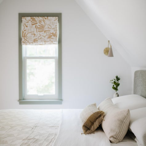 Primary bedroom featuring custom window treatments, vintage textiles and brass task lighting