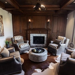 Library with hair-on-hide rug, leather chairs, stone fireplace, stained cabinets