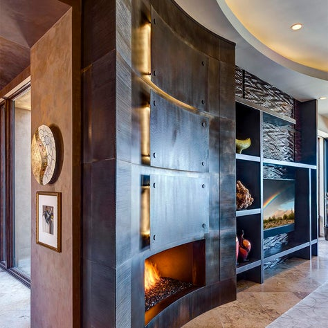 The curved wall that surrounds the actual fireplace is artistic and functional