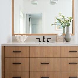 Pebble Beach bathroom vanity. Wood drawers, dark hardware, and Heath Ceramics.