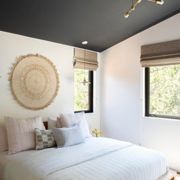 Platform bed, contemporary lighting, and dark blue-grey painted ceiling in bright master bedroom