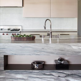 Lathered quartzite in earth tones with a fluid pattern on island.