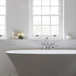 Luxury master bathroom featuring freestanding bath, carrera marble