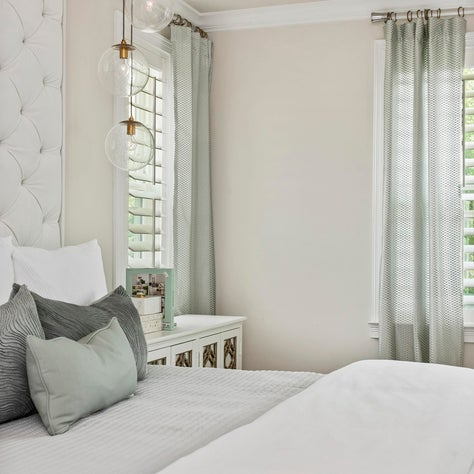 Tufted, upholstered wall w/ contemporary glass orb pendant lighting over bed.