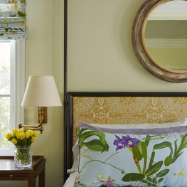 Vibrant layering of patterns in this traditional, coastal master bedroom