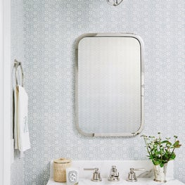 Blue and white wallpapered powder room with marble vanity and polished nickel fixtures