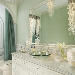 The bathroom shimmers with glass beaded wallpaper, hung above a marble wainscot.  The vanity features a mirrored-glass vessel sink and spherical glass knobs backed by mirrored plates.  Lighting is sconces and a dramatic ceiling fixture of crystal strands