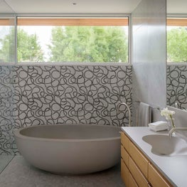 Freestanding concrete tub with carved marble wall tile