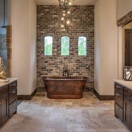 Copper hammered tub in this spectacular master bath with electric mirrors