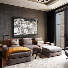 Dramatic Chelsea Media Room with grasscloth wallpaper and plush furnishing