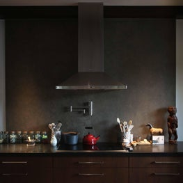 Spanish contemporary residence stove and hood in dark grays, metal, and wood