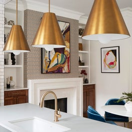 White kitchen with subway tile backsplash, quartz countertops, marble dining table, oversized pendants, large windows, blue chairs, walnut cabinets, geometric wallpaper, marble fireplace