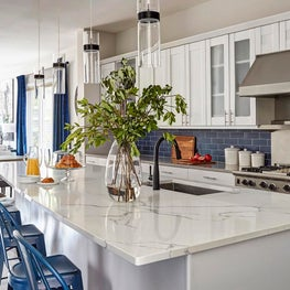 White Kitchen with Blue Wall Tile, White Quartz Countertops and Black Accents