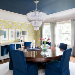 A Dining Room with preppy, vintage charmer - complete with blue velvet chairs, cheerful wallpaper and watercolor art works.