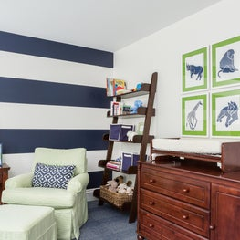 Nursery is accented with bold navy-striped wallpaper and lime green decor