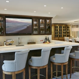 Open plan with relaxed custom cabinetry bar space adjacent to the dining room.