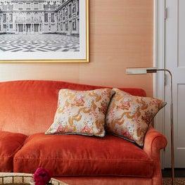 Detail shot of orange sofa, orange wallpaper in sitting room