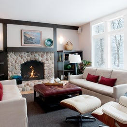 Family Room stone fireplace, built ins & lake view. Linen sofas with Eames Chair