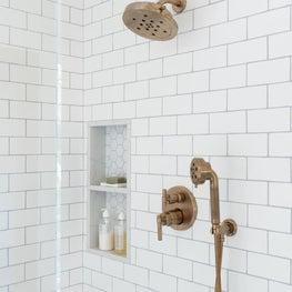 bathroom shower brushed gold fixtures/white subway tile/shower niche
