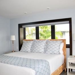 master bedroom/rattan bed/gold light fixtures/blue and white bedding
