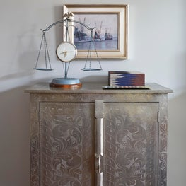 Vignette with metal cabinet, oil painting, accessories and vintage scale clock